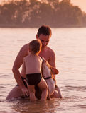 Vater und Sohn voll herum mit Spürhundhund im Flusswasser Lizenzfreie Stockfotos