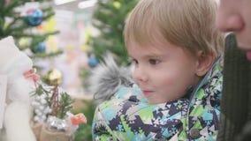 Vater und Sohn wählen ein Weihnachtsgeschenk im Speicher Weihnachtsverkauf von Spielwaren und von Weihnachtsbäumen bis Weihnachte stock video footage