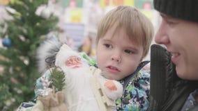 Vater und Sohn wählen ein Weihnachtsgeschenk im Speicher Weihnachtsverkauf von Spielwaren und von Weihnachtsbäumen bis Weihnachte stock footage