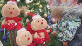 Vater und Sohn wählen einen Weihnachtsbaum im Speicher Weihnachtsverkauf von Spielwaren und von Weihnachtsbäumen bis Weihnachten stock video footage
