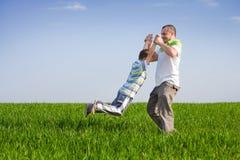 Vater und Sohn, welche die gute Zeit im Freien hat Stockbilder