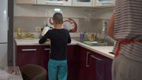 Vater- und Sohnanfang, der Lebensmittel kocht Vati schickt ihrem Sohn ein Küchenbrett stock video footage