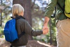 Vater- und Sohnhändchenhalten beim Wandern im Wald Stockfotografie