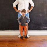 Vater- und Sohnhände auf Taille Stockfotografie