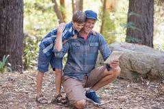Vater- und Sohnlesung zeichnen beim Wandern im Wald auf Stockbild
