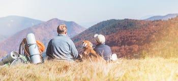 Vater- und Sohnreisende mit ihrem Spürhundhund sitzen zusammen im Gebirgstal mit schöner Hügelansicht Trekking mit Kindern und lizenzfreie stockfotos