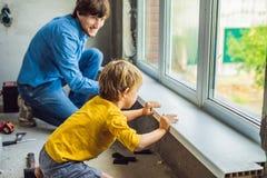 Vater- und Sohnreparaturfenster zusammen Reparieren Sie das Haus sich stockfotos