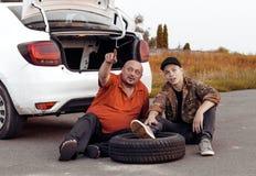 Vater- und Sohnrest während der Autoreparaturen stockbild