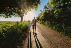 Vater- und Sohnweg auf Sonnenuntergangstraße Lizenzfreies Stockfoto
