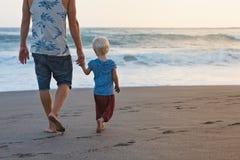 Vater- und Sohnwege auf Sonnenuntergangozean setzen auf den Strand Stockbild
