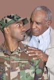 Vater und Soldat US Marine Corps, der einander über braunem Hintergrund betrachtet Lizenzfreie Stockfotos