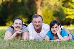 Vater und Töchter auf Gras Stockbilder
