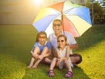 Vater und Töchter, die auf einer Wiese mit buntem Regenschirm sitzen Stockbilder