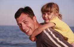 Vater und Tochter auf dem Seeufer Stockbild