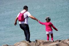 Vater und Tochter auf den Felsen in Richtung zum Meer Lizenzfreies Stockfoto