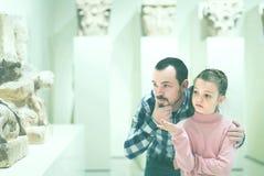 Vater und Tochter, die alte Flachreliefs im Museum betrachten Lizenzfreies Stockbild