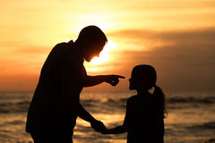 Vater und Tochter, die auf dem Strand zur Sonnenuntergangzeit spielen Lizenzfreie Stockfotografie