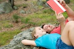 Vater und Tochter, die auf Felsen und dem Ablesen liegen Stockfotografie