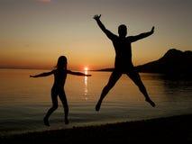 Vater und Tochter, die in den Sonnenuntergang springen Stockfotos