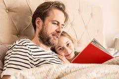 Vater und Tochter, die ein Buch in einem Bett lesen lizenzfreies stockbild