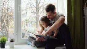 Vater und Tochter, die ein Buch lesen stock video