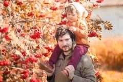 Vater und Tochter, die einen Spaß im Herbstpark haben Stockfotos