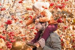 Vater und Tochter, die einen Spaß im Herbstpark haben Lizenzfreies Stockbild