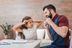 Vater und Tochter, die Hörner und Reißzähne von den Bleistiften beim zu Hause zeichnen machen Stockfoto