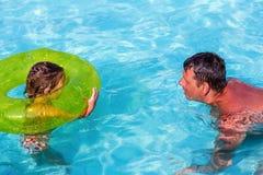 Vater und Tochter, die im Swimmingpool spielen Lustige Ferien des Sommers stockfotografie