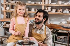 Vater und Tochter, die keramischen Topflehrer malen lizenzfreie stockbilder