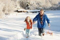 Vater und Tochter, die Schlitten herauf Snowy-Hügel ziehen Stockbild