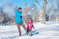 Vater und Tochter, die Schneeball spielen Stockbild