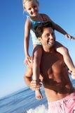 Vater und Tochter, die Spaß auf Strand haben Stockbilder
