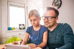 Vater und Tochter, die Tablette verwendet Lizenzfreie Stockfotografie