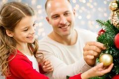 Vater und Tochter, die Weihnachtsbaum verzieren lizenzfreie stockbilder