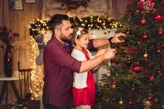 Vater und Tochter, die Weihnachtsbaum verzieren stockfotos