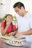 Vater und Tochter, die zusammen Sushi zubereiten stockbilder