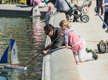 Vater und Tochter drücken Spielzeugsegelboot im Brunnen in Luxemburg-Garten, Paris, Frankreich Lizenzfreie Stockfotos