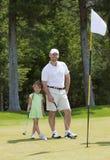 Vater-und Tochter-Golf spielen stockfotografie