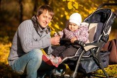 Vater und Tochter im Buggy am Herbst parken stockfoto