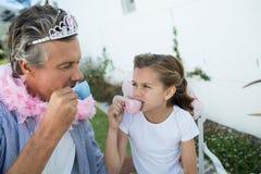 Vater und Tochter im feenhaften Kostüm, das eine Teeparty hat stockbild