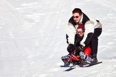 Vater-und Tochter-Spaß-Schlitten-Fahrt Lizenzfreies Stockfoto