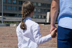 Vater und Tochter stehen mit ihren Rückseiten, Händchenhalten vor der Schule lizenzfreie stockbilder