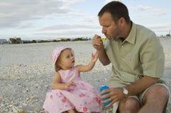 Vater und Tochter am Strand Stockbilder
