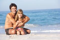 Vater-und Tochter-tragende Badebekleidung, die sich hinsitzt Lizenzfreies Stockfoto