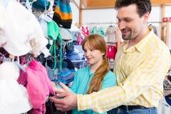 Vater- und Tochtereinkaufskleidung im Einzelhandelsgeschäft stockbilder