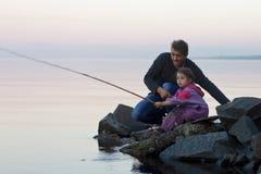 Vater- und Tochterfischen bei Sonnenuntergang auf See Stockfotografie