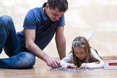 Vater- und Tochterpuzzlespiel Stockfotos