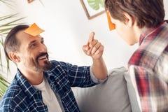 Vater und wenig Sohn zu Hause, die auf dem Sofa spielt die Stirndetektiv-Vatinahaufnahme zeigt auf den Aufkleber des Jungen spiel stockbild