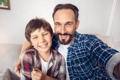 Vater und wenig Sohn zu Hause, die selfie nehmend auf dem Smartphone schaut frohe Nahaufnahme der Kamera sitzt stockfoto
